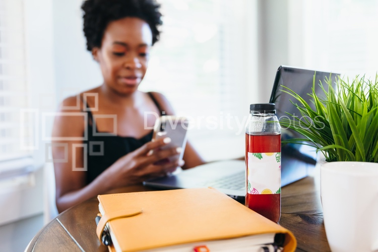 Woman working remotely from home on smartphone with wellness drink