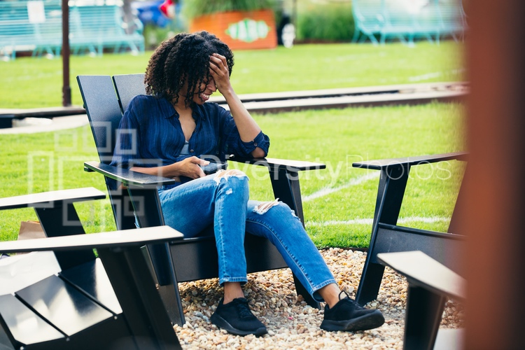 Laughing black woman sitting in patio chair by outdoor fire pit