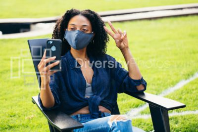 Black woman sitting in patio chair  with a face mask taking a selfie during covid 19