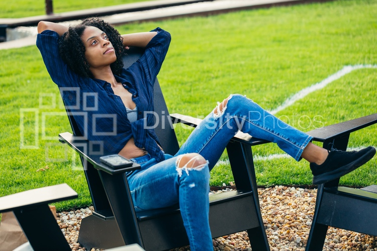 Black woman relaxing in chair near fire pit