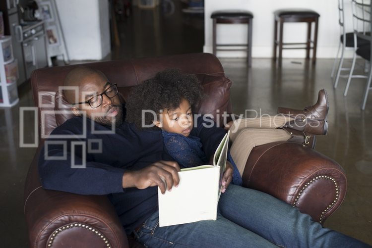 Black Father and Daughter Sitting and Reading together