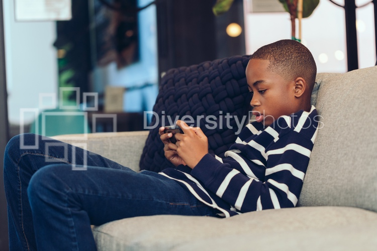 Black kid playing game on phone