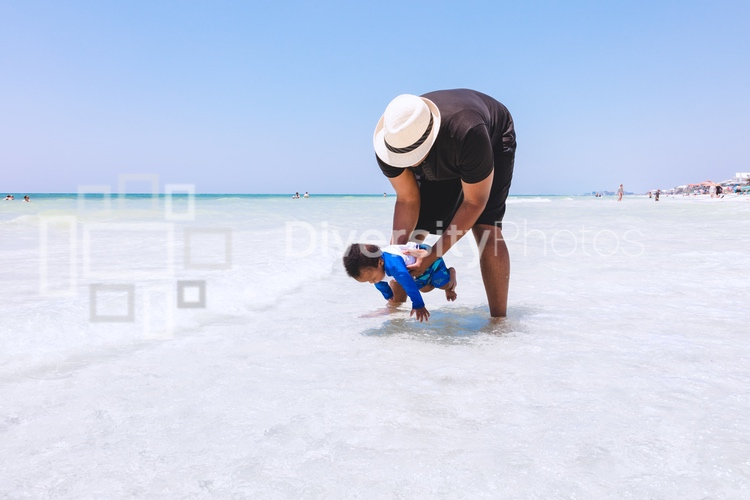 Black father playing with son in shallow water