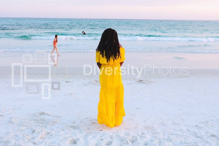 Black woman in pretty sun dress on the beach