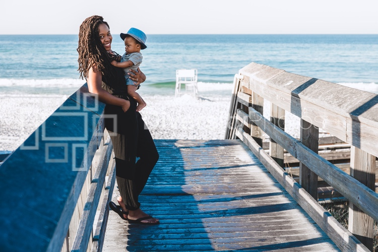 Black mom and son on boardwalk