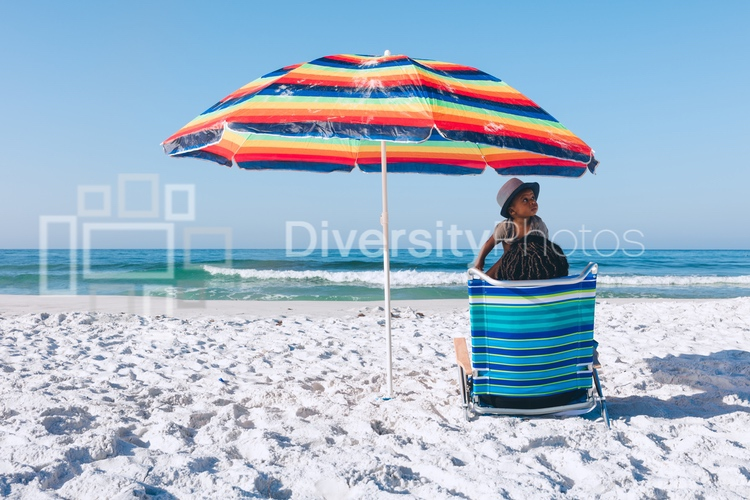 Black mother and son sitting on beach