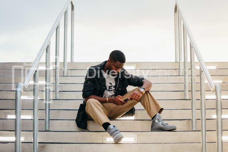 Young man on phone sitting stairs