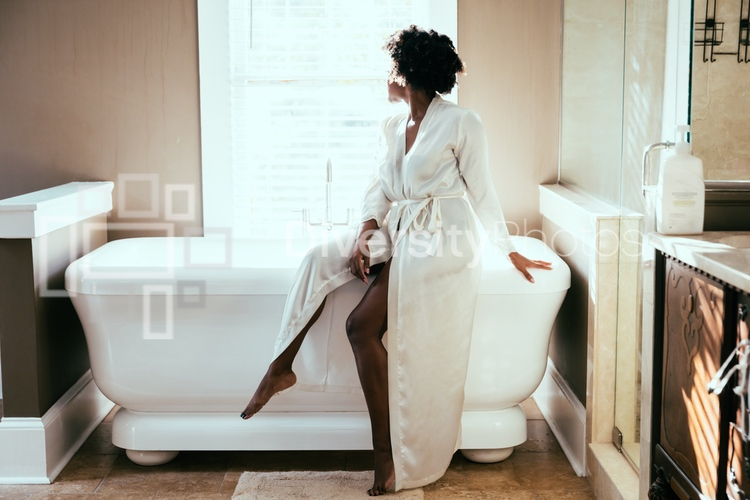 Attractive woman with natural hair prepares for bath