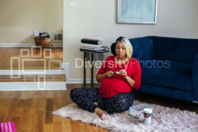 Pregnant black woman with blonde hair eating healthy snack at home