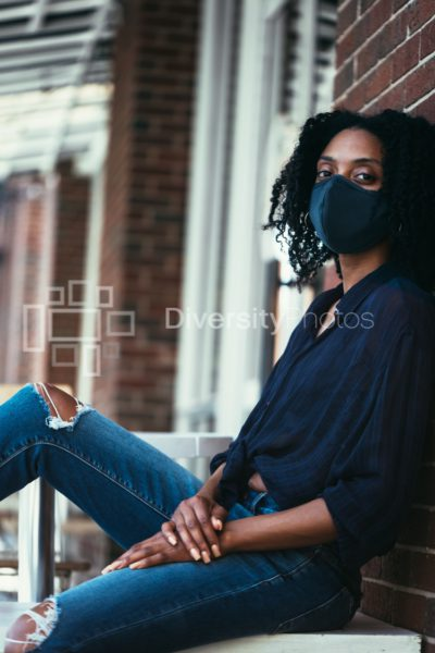 Black woman in mask during covid-19 sitting against wall for outdoor portrait