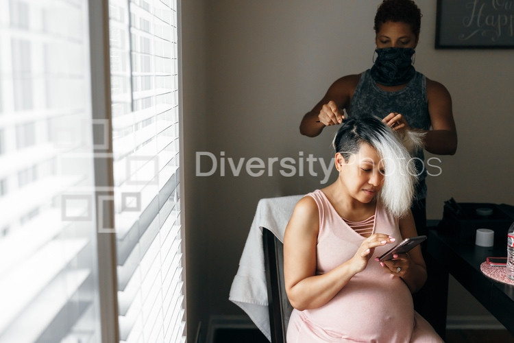 Pregnant black woman having hair done and self-care by hairdresser in mask during Covid-19