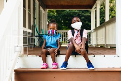 Siblings getting ready to go to school wearing masks