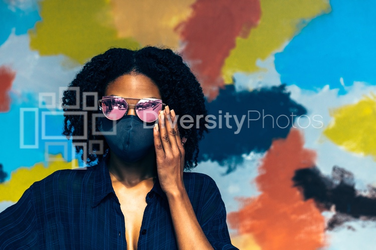 Black woman with natural hair wearing mask and sunglasses in front of mural