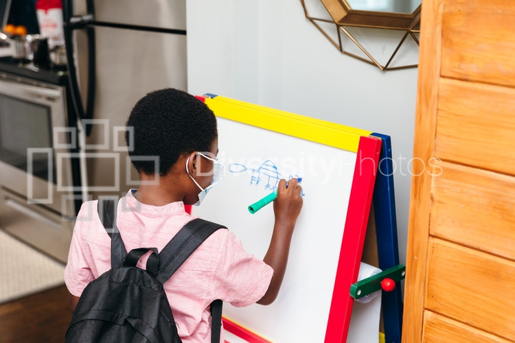 Young boy drawing on board at home for school