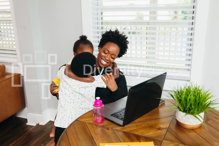 Kids hugging mom while she is working from home on video chat