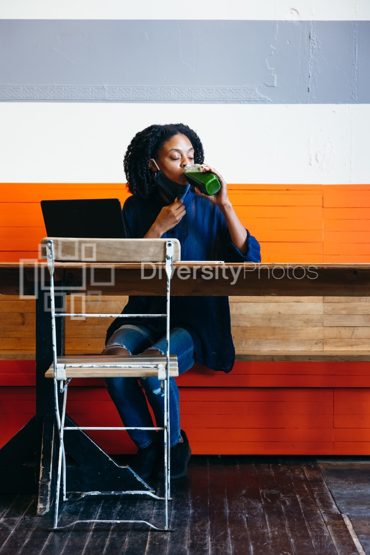 Black woman working at cafe on laptop with face mask during covid-19