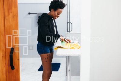 Woman doing house chores ironing children's clothes
