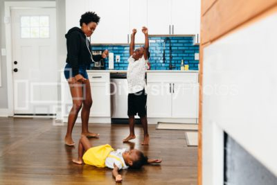 Mother, son and daughter playing and dancing in the kitchen at home