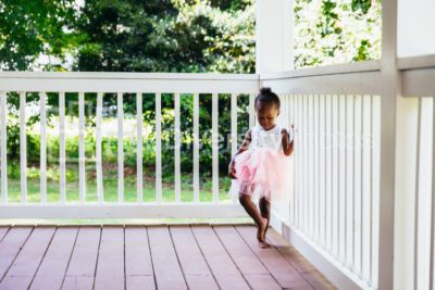 Young ballerina playing on front porch at home