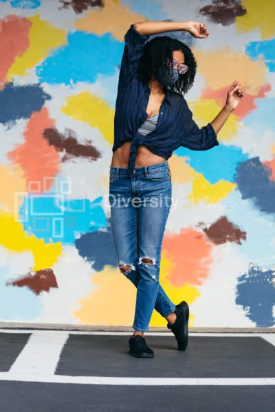 Black woman with natural hair wearing mask and sunglasses dancing in front of mural