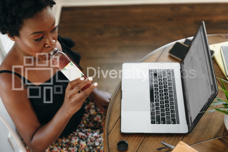 Woman working remotely from home drinking a healthy drink
