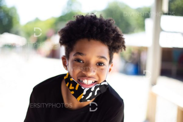 Happy and smiling black boy outside at park