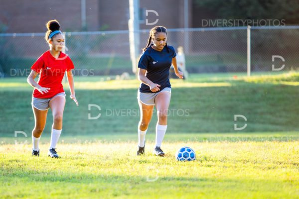 Teenage girl soccer players running after ball