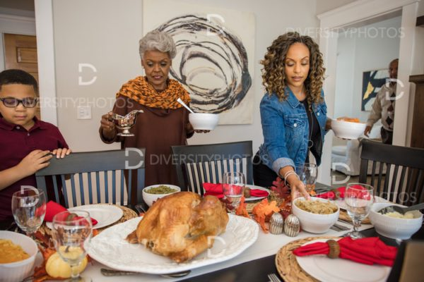 Black multigenerational family setting table for Thanksgiving  holiday meal