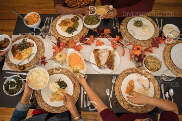 Overhead view of black hands eating Thanksgiving holiday meal