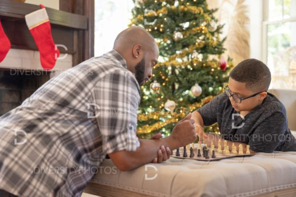 Black father and son playing chess together